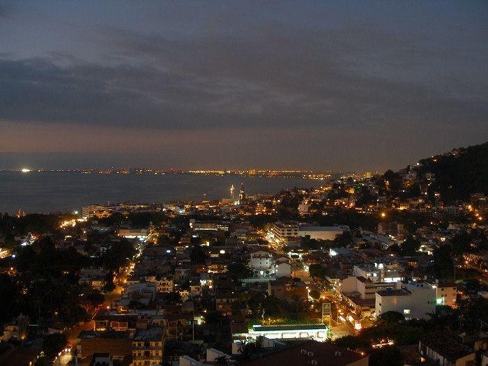 «Puerto vallarta at night» de Coolcaesar de en.wikipedia.org. Disponible bajo la licencia CC BY-SA 3.0 vía Wikimedia Commons - https://commons.wikimedia.org/wiki/File:Puerto_vallarta_at_night.jpg#/media/File:Puerto_vallarta_at_night.jpg